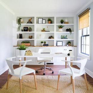 Modelo de despacho tradicional renovado, grande, sin chimenea, con suelo de madera en tonos medios, escritorio independiente, suelo marrón y paredes blancas