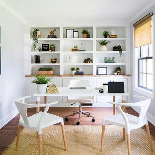 ローリーの大きいトランジショナルスタイルのおしゃれな書斎 (無垢フローリング、暖炉なし、自立型机、茶色い床、白い壁) の写真