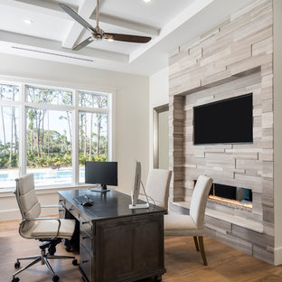 Example of a trendy freestanding desk medium tone wood floor and brown floor home office design in Miami with white walls and a ribbon fireplace