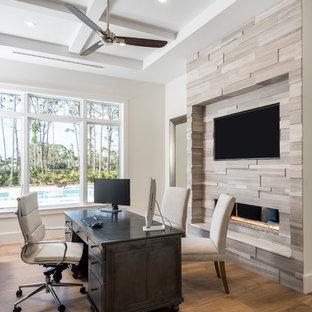 マイアミのコンテンポラリースタイルのおしゃれなホームオフィス・書斎 (白い壁、無垢フローリング、横長型暖炉、自立型机、茶色い床) の写真