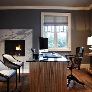 Неиссякаемый источник вдохновения для домашнего уюта: большое рабочее место в современном стиле с серыми стенами, паркетным полом среднего тона, стандартным камином, отдельно стоящим рабочим столом, фасадом камина из камня и коричневым полом