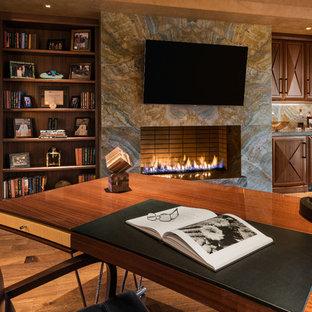 Inspiration för ett stort funkis hemmabibliotek, med bruna väggar, ljust trägolv, en bred öppen spis, en spiselkrans i sten och ett fristående skrivbord