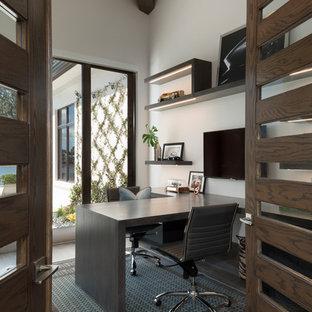 На фото: кабинет среднего размера в стиле модернизм с бежевыми стенами, темным паркетным полом, встроенным рабочим столом и коричневым полом без камина с
