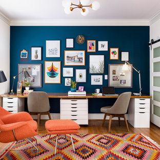 Стильный дизайн: рабочее место среднего размера в стиле фьюжн с встроенным рабочим столом, синими стенами, паркетным полом среднего тона и коричневым полом - последний тренд