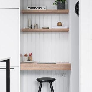 Großes Modernes Arbeitszimmer mit Betonboden, grauem Boden, weißer Wandfarbe und Einbau-Schreibtisch in Sydney
