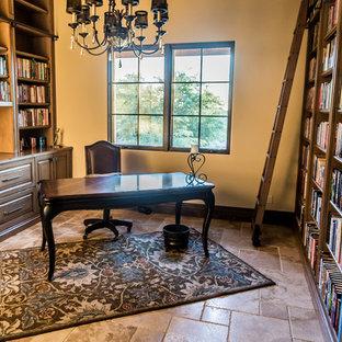 Esempio di un ampio studio country con libreria, pareti beige, pavimento in travertino, camino classico, cornice del camino in pietra, scrivania autoportante e pavimento multicolore