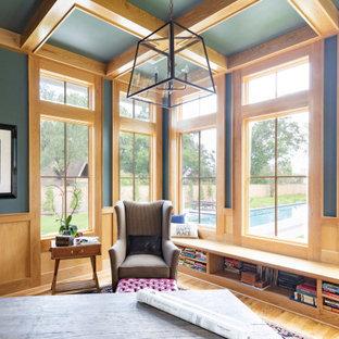 ヒューストンの大きいカントリー風おしゃれなホームオフィス・書斎 (ライブラリー、青い壁、淡色無垢フローリング、標準型暖炉、レンガの暖炉まわり、自立型机、ベージュの床) の写真