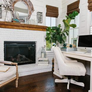 Aménagement d'un bureau bord de mer de taille moyenne avec un mur blanc, un sol en bois foncé, une cheminée standard, un manteau de cheminée en brique et un bureau indépendant.