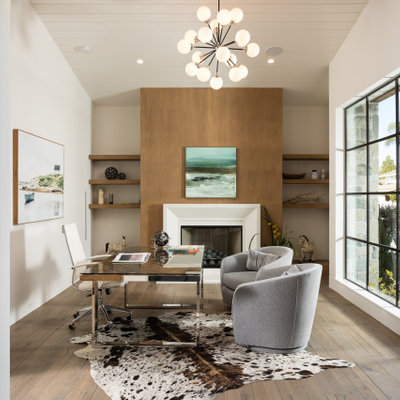 Study room - cottage freestanding desk medium tone wood floor and brown floor study room idea in Orange County with white walls, a standard fireplace and a wood fireplace surround
