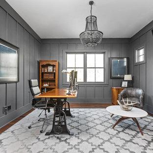 Diseño de despacho campestre con paredes grises, suelo de madera oscura, chimenea lineal, marco de chimenea de metal y escritorio independiente
