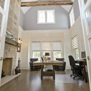 Immagine di un ufficio minimalista con pareti grigie, parquet chiaro, camino classico, cornice del camino in pietra e scrivania autoportante
