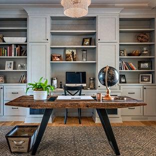 Mittelgroßes Country Arbeitszimmer ohne Kamin mit Arbeitsplatz, grauer Wandfarbe, braunem Holzboden, freistehendem Schreibtisch und braunem Boden in Nashville