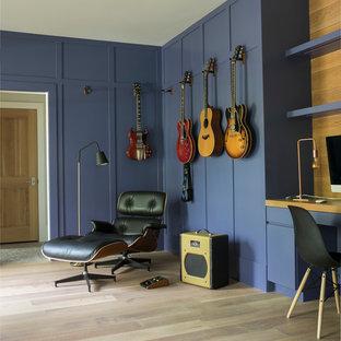 ニューヨークのカントリー風おしゃれなホームオフィス・仕事部屋 (青い壁、淡色無垢フローリング、造り付け机、ベージュの床) の写真