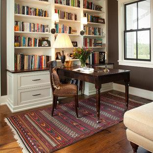 Immagine di uno studio classico con libreria, pareti marroni, pavimento in legno massello medio e scrivania autoportante