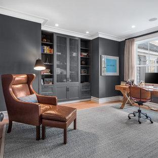 Mittelgroßes Klassisches Arbeitszimmer ohne Kamin mit grauer Wandfarbe, braunem Holzboden, freistehendem Schreibtisch, braunem Boden und Arbeitsplatz in New York