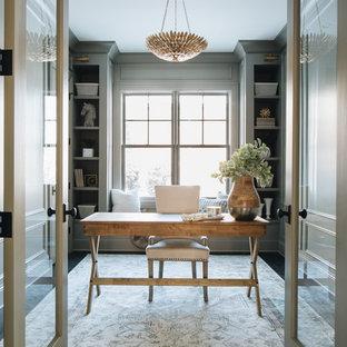 Landhaus Arbeitszimmer mit grauer Wandfarbe, dunklem Holzboden, freistehendem Schreibtisch und braunem Boden in Chicago