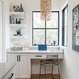 Design ideas for a rural study in Austin with yellow walls, light hardwood flooring, no fireplace, a built-in desk and beige floors.