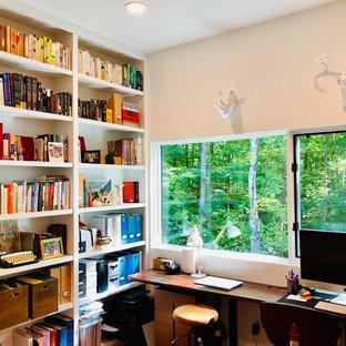 Immagine di uno studio minimal con libreria, pareti bianche e scrivania autoportante