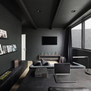 Esempio di uno studio minimalista con pareti nere e parquet chiaro