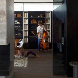 シカゴの中くらいのコンテンポラリースタイルのおしゃれな書斎 (無垢フローリング、両方向型暖炉、石材の暖炉まわり) の写真