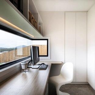 Esempio di un piccolo ufficio minimalista con pareti bianche, moquette e scrivania incassata