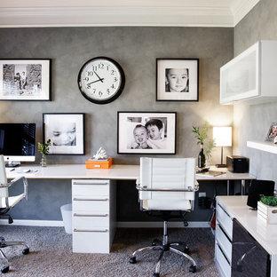 Стильный дизайн: маленькое рабочее место в стиле модернизм с серыми стенами, ковровым покрытием и отдельно стоящим рабочим столом - последний тренд