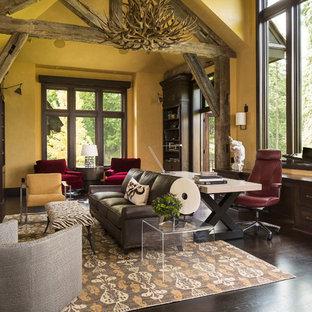 Rustik inredning av ett arbetsrum, med gula väggar, mörkt trägolv, en standard öppen spis och ett fristående skrivbord