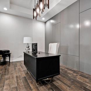 Idéer för att renovera ett stort funkis hemmabibliotek, med grå väggar, klinkergolv i porslin, ett fristående skrivbord och brunt golv