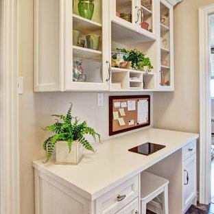Diseño de despacho tradicional, pequeño, con suelo de linóleo, paredes beige y escritorio empotrado