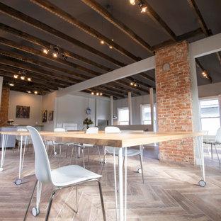 На фото: огромная домашняя мастерская в стиле рустика с серыми стенами, полом из керамической плитки, отдельно стоящим рабочим столом, бежевым полом, балками на потолке и кирпичными стенами без камина