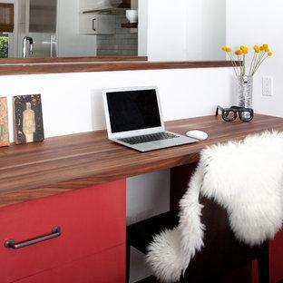Стильный дизайн: кабинет в стиле ретро с белыми стенами, темным паркетным полом и встроенным рабочим столом - последний тренд