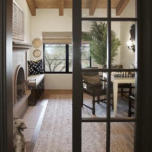 Diseño de despacho madera, tradicional, con suelo de madera en tonos medios, chimenea tradicional, marco de chimenea de piedra, suelo marrón, paredes blancas y escritorio independiente