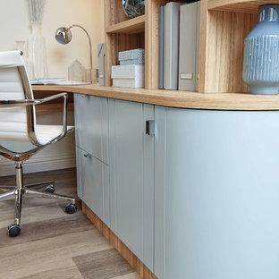 他の地域の小さいトランジショナルスタイルのおしゃれな書斎 (白い壁、ラミネートの床、造り付け机、茶色い床) の写真