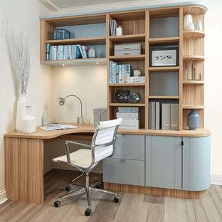 他の地域の小さいトランジショナルスタイルのおしゃれな書斎 (白い壁、ラミネートの床、造り付け机、ベージュの床) の写真