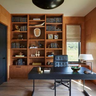 Cette photo montre un grand bureau tendance en bois avec un mur marron, un sol en bois clair, un bureau indépendant, un sol marron et aucune cheminée.