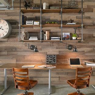 Foto på ett stort industriellt arbetsrum, med betonggolv, ett fristående skrivbord, grått golv och bruna väggar