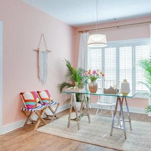 Exotisk inredning av ett litet hemmabibliotek, med rosa väggar, ljust trägolv, ett fristående skrivbord och beiget golv