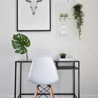 Aménagement d'un petit bureau scandinave avec un mur blanc, sol en stratifié, un bureau indépendant et un sol gris.