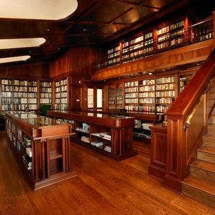 Diseño de despacho clásico, extra grande, con suelo de madera en tonos medios y escritorio empotrado