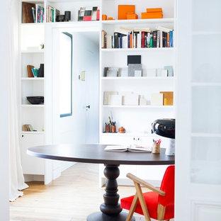 Exemple d'un bureau tendance de taille moyenne avec un bureau indépendant, un mur blanc et un sol en bois brun.