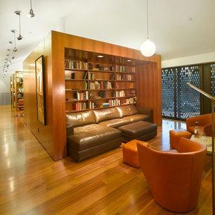 ロサンゼルスの巨大なモダンスタイルのおしゃれなホームオフィス・書斎 (ライブラリー、白い壁、無垢フローリング、自立型机) の写真