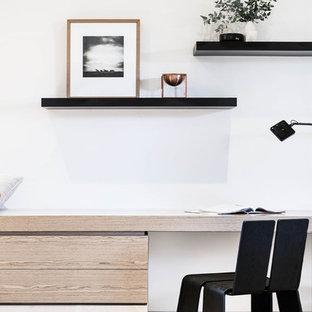 Modelo de despacho minimalista, de tamaño medio, con paredes blancas, suelo de piedra caliza y escritorio empotrado