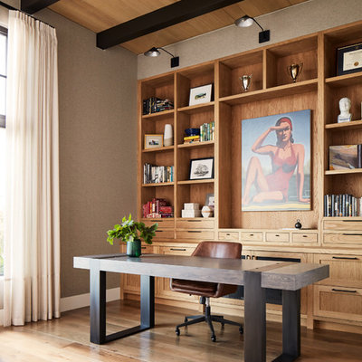 Transitional freestanding desk medium tone wood floor and brown floor home office photo in San Francisco with gray walls