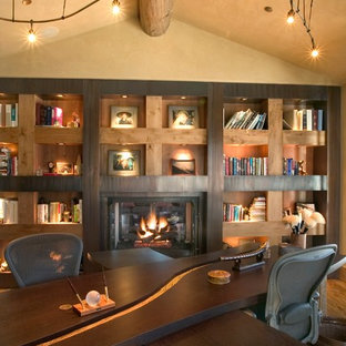 Modern home office and library in Denver with beige walls, medium hardwood flooring, a standard fireplace, a metal fireplace surround and a freestanding desk.
