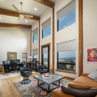 Идея дизайна: домашняя мастерская среднего размера в стиле рустика с белыми стенами, светлым паркетным полом, стандартным камином, фасадом камина из плитки, отдельно стоящим рабочим столом и балками на потолке
