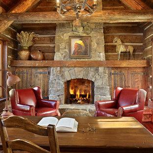 Rustik inredning av ett mellanstort arbetsrum, med mellanmörkt trägolv, en standard öppen spis, en spiselkrans i sten och ett fristående skrivbord
