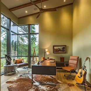 Idéer för att renovera ett stort funkis hemmabibliotek, med gröna väggar, ljust trägolv och ett fristående skrivbord