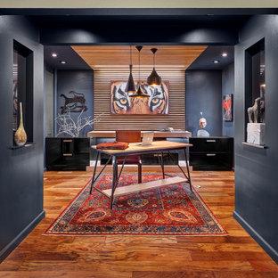 Foto de despacho madera, actual, grande, madera, con paredes negras, suelo de madera en tonos medios, escritorio independiente, madera y suelo marrón