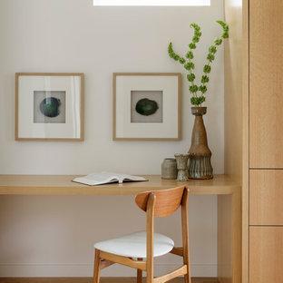 Esempio di uno studio minimal con pareti bianche, pavimento in legno massello medio, scrivania incassata e pavimento marrone