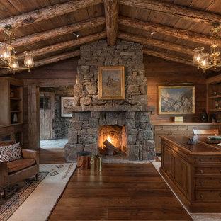 Bild på ett rustikt hemmabibliotek, med mellanmörkt trägolv, en standard öppen spis, en spiselkrans i sten och ett fristående skrivbord